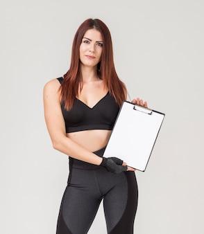 Vista frontal da mulher atlética segurando o bloco de notas