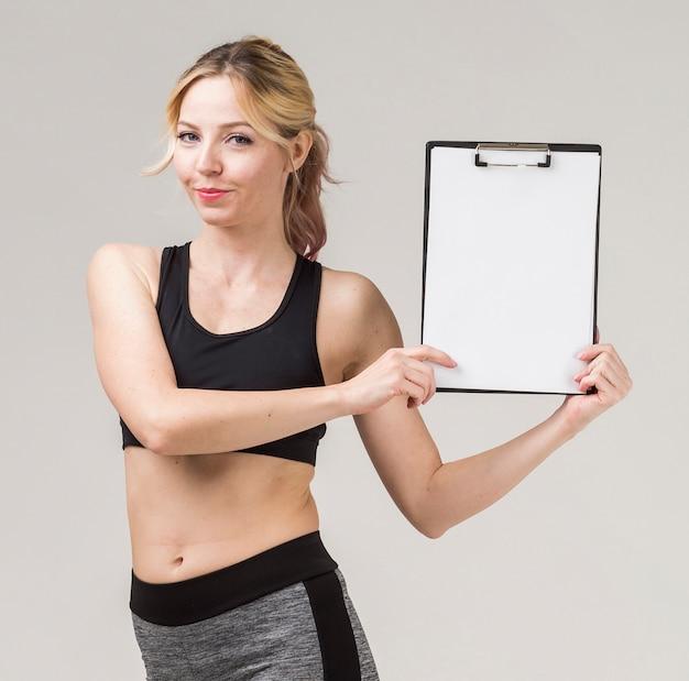 Vista frontal da mulher atlética, sorrindo e segurando o bloco de notas