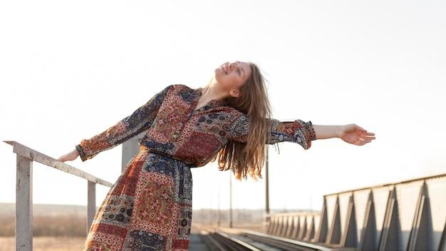 Vista frontal da mulher boêmia posando pelos trilhos do trem