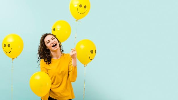 Vista frontal da mulher bonita com balões