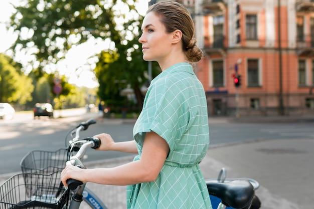 Vista frontal da mulher bonita com bicicleta