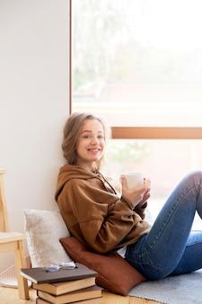 Vista frontal da mulher bonita, relaxando em casa