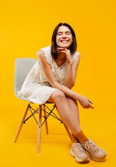 Vista frontal da mulher bonita sentada na cadeira
