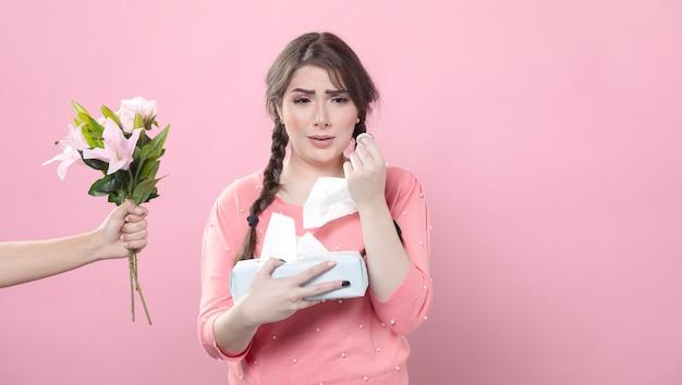 Vista frontal da mulher chorando, sendo oferecido buquê de lírios, segurando guardanapos