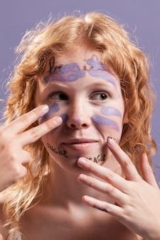Vista frontal da mulher cobrindo palavras com tinta
