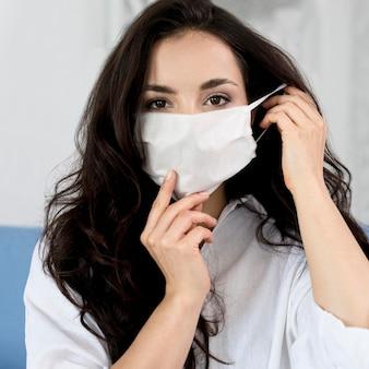 Vista frontal da mulher colocando máscara facial
