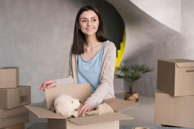 Vista frontal da mulher colocando o ursinho de pelúcia na caixa para enviar
