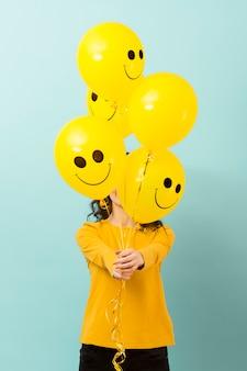 Vista frontal da mulher com balões