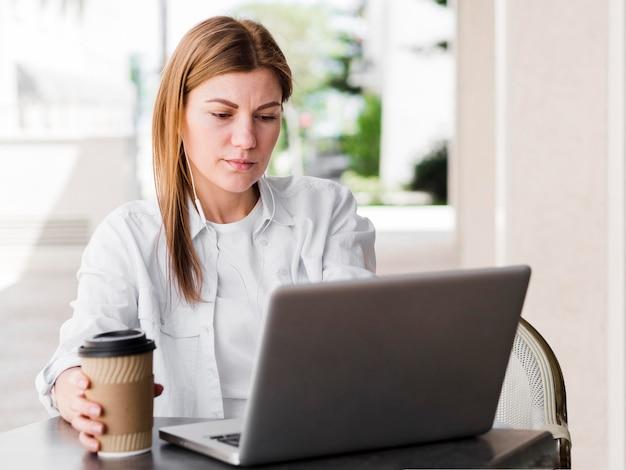 Vista frontal da mulher com café e fones de ouvido trabalhando no laptop ao ar livre