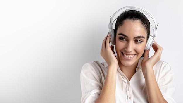 Vista frontal da mulher com fones de ouvido sorrindo