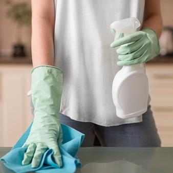 Vista frontal da mulher com luvas de limpeza, segurando o pano e a solução de limpeza