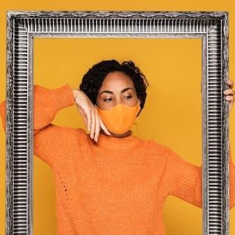 Vista frontal da mulher com máscara e moldura