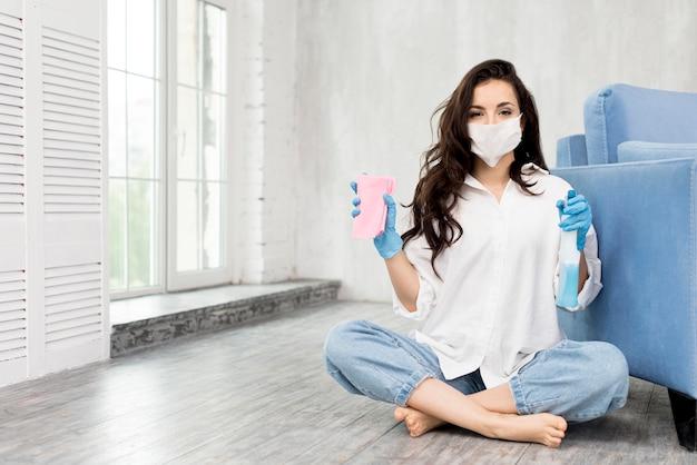 Vista frontal da mulher com máscara facial segurando a solução de limpeza