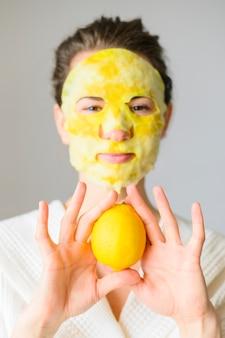Vista frontal da mulher com máscara facial segurando um limão