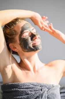 Vista frontal da mulher com máscara facial, tomando sol ao sol em casa