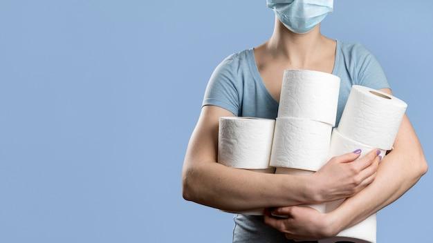 Vista frontal da mulher com máscara médica segurando vários rolos de papel higiênico