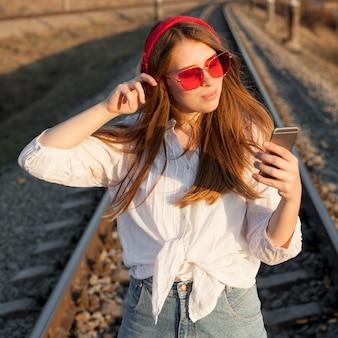 Vista frontal da mulher com óculos de sol, olhando para smartphone em trilhos de trem