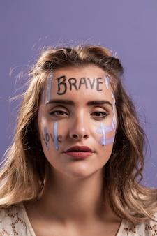 Vista frontal da mulher com palavras pintadas no rosto