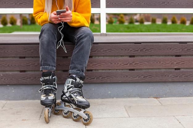 Vista frontal da mulher com patins segurando o smartphone