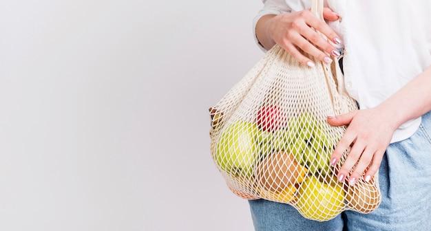 Vista frontal da mulher com saco de frutas