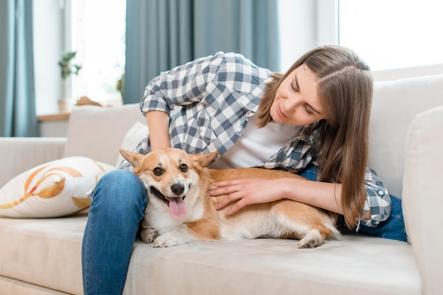 Vista frontal da mulher com seu cachorro no sofá