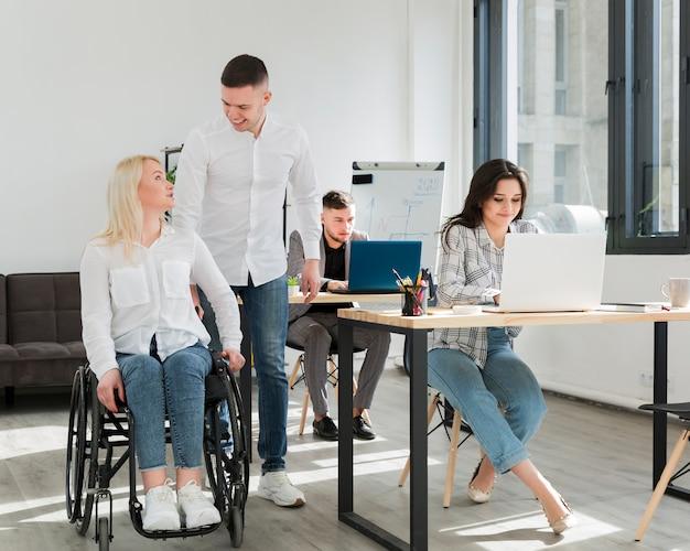 Vista frontal da mulher com seus colegas de trabalho no escritório