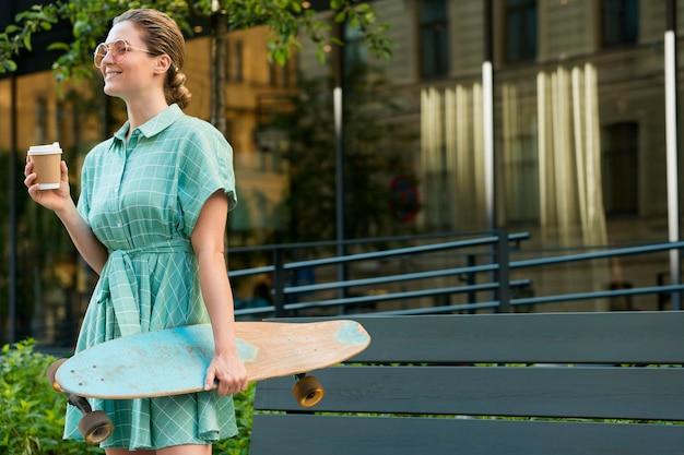 Vista frontal da mulher com skate