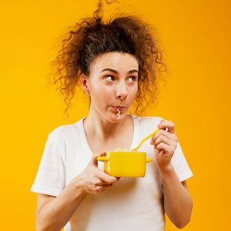 Vista frontal da mulher comendo macarrão