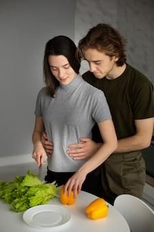 Vista frontal da mulher cortando legumes com namorado