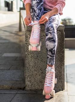 Vista frontal da mulher de caneleiras com patins