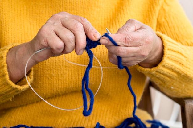 Vista frontal da mulher de crochê com fios