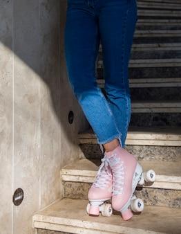 Vista frontal da mulher de jeans nas escadas com patins
