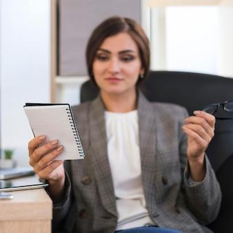 Vista frontal da mulher de negócios desfocada, olhando para o caderno