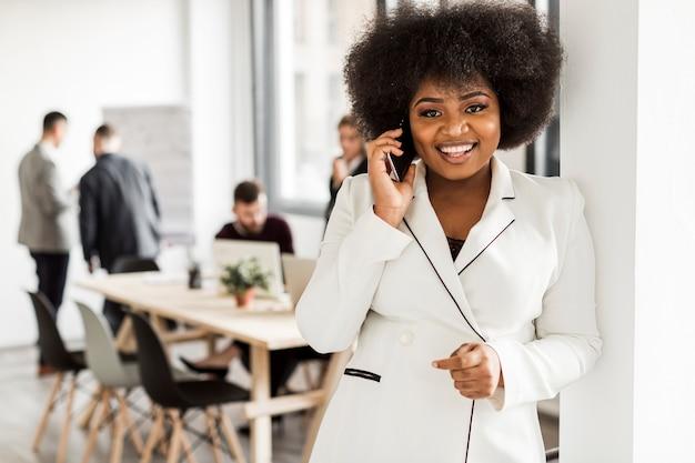 Vista frontal da mulher de negócios, falando no telefone