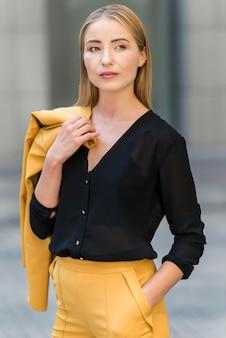 Vista frontal da mulher de negócios, posando ao ar livre no terno