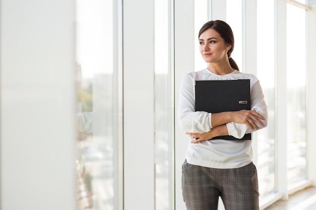 Vista frontal da mulher de negócios posando enquanto segura a pasta