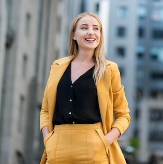 Vista frontal da mulher de negócios sorridente no terno ao ar livre