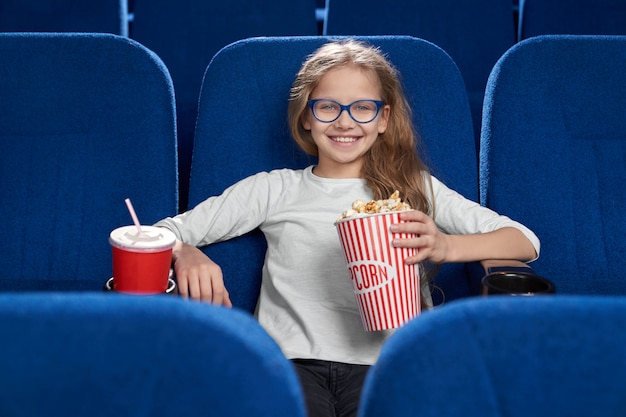 Vista frontal da mulher de óculos no cinema