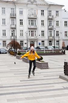 Vista frontal da mulher de patins na cidade
