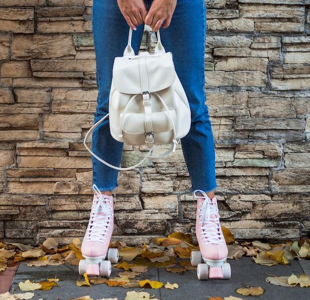 Vista frontal da mulher de patins segurando a mochila