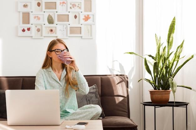 Vista frontal da mulher de pijama segurando caneca e trabalhando em casa