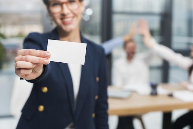 Vista frontal da mulher de recursos humanos segurando o cartão de visita