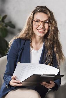 Vista frontal da mulher de recursos humanos segurando papéis