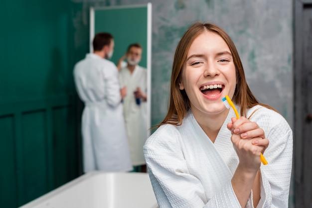 Vista frontal da mulher de roupão cantando na escova de dentes