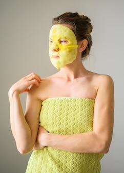 Vista frontal da mulher de toalha com máscara facial