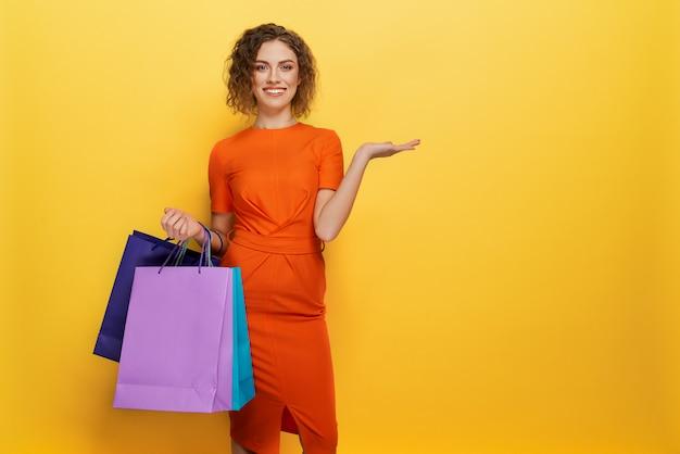 Vista frontal da mulher de vestido laranja, mantendo sacos de papel