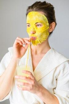 Vista frontal da mulher desfrutando de uma bebida enquanto estiver com uma máscara facial