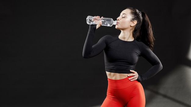 Vista frontal da mulher desportiva água potável