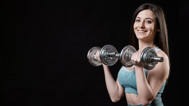 Vista frontal da mulher desportiva com halteres