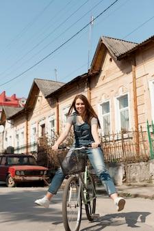 Vista frontal da mulher despreocupada, andar de bicicleta